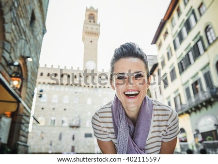 It's time to tick off must-see Florence treasures of a bucket list. Portrait of smiling young woman tourist in the front of Palazzo Vecchio in Florence, Italy - stock photo