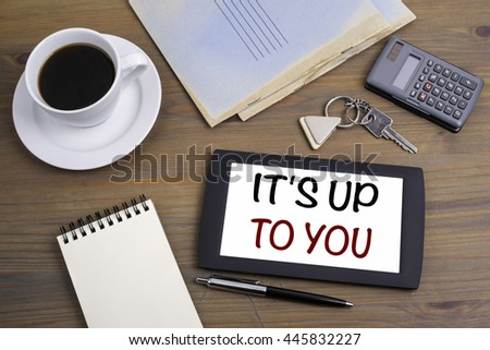 It's Up To You. Text on tablet device on a wooden table - stock photo