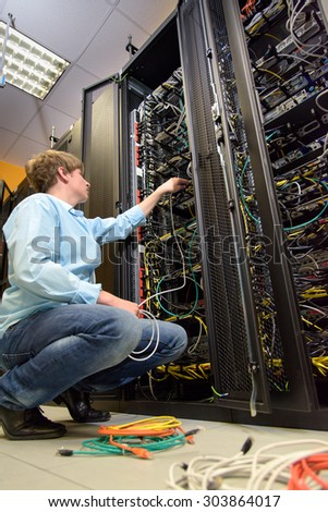 IT specialist installing cables in datacenter by open rack of patch panels - stock photo