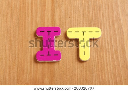 IT, spell by woody puzzle letters with woody background - stock photo