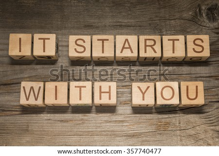 It starts with you text on a wooden background - stock photo