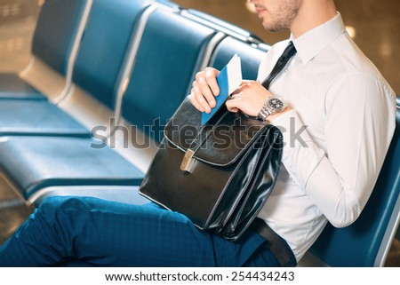 It was a long business trip. Cropped image of an exhausted business man in formalwear sleeping while sitting on the rows of chairs in the airport holding his business case and passport - stock photo