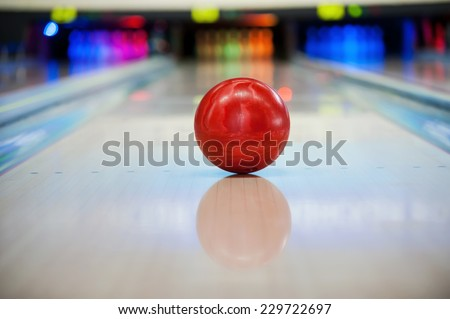 It will be strike! Close-up of bright red bowling ball rolling along bowling alley   - stock photo