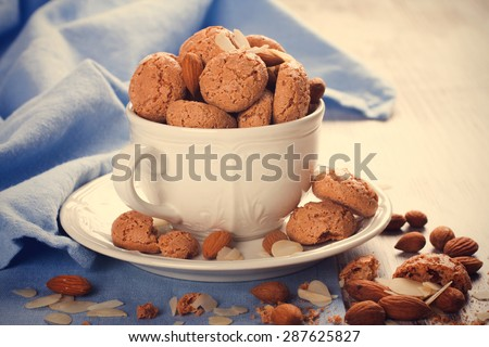 Italian almond cookie amaretti in white coffee cup with almonds on white table with blue napkin, selective focus. retro style toned. - stock photo