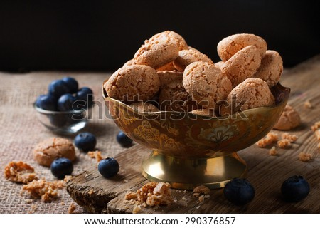 Italian almond cookie amaretti with blueberries on rustic wooden board, selective focus, law key. - stock photo