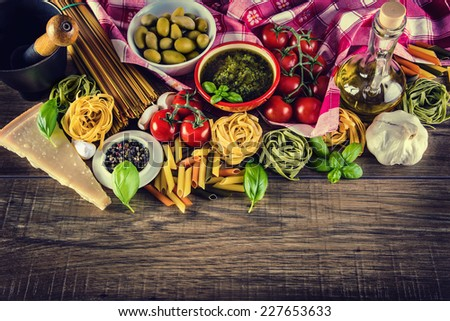 Italian and Mediterranean food ingredients on old wooden background.spaghetti olives basil cherry tomato pesto pasta garlic pepper olive oil and mortar. - stock photo