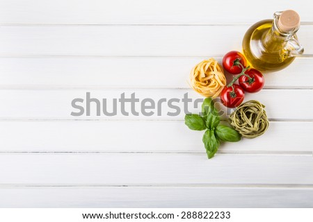 Italian and Mediterranean food ingredients on white wooden background.Cherry tomatoes pasta, basil leaves and carafe with olive oil - stock photo
