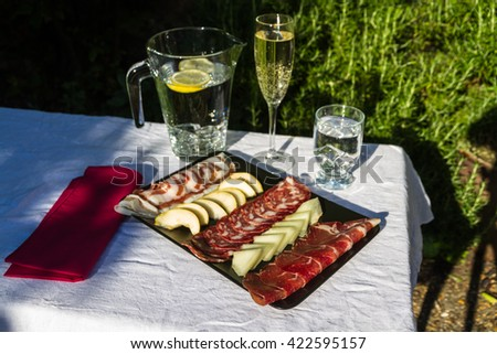 Italian antipasto meat platter outside in evening light.  Salami, ham, pancetta, pear and melon. Served with iced water. - stock photo