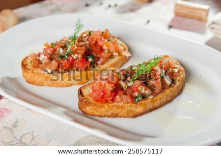 Italian Appetizer Bruschetta with roasted tomatoes, basil, garlic and herbs on slices of crisp crusty toasted or grilled baguette lying on the white plate  low angle view with shallow dof - stock photo