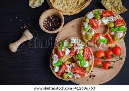 Italian appetizer Friselle. Italian dried bread Friselle on wooden board with tomatoes cherry, olives, tuna, basil and peppercorns. Italian food. A quick and easy snack for party time.  - stock photo