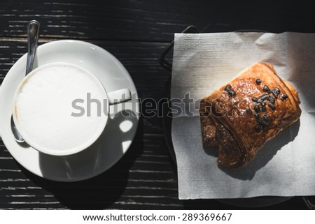 Italian breakfast with cappuccino and chocolate brioches on a black wooden table - stock photo