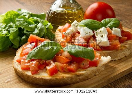 italian bruschetta with fresh tomatoes, basil, garlic, olive oil and cheese - stock photo