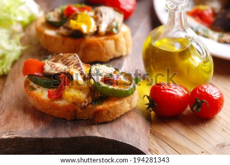 Italian bruschetta with grilled vegetables on wooden board - stock photo