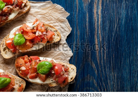 Italian bruschetta with roasted tomatoes, mozzarella cheese and herbs on a paper - stock photo