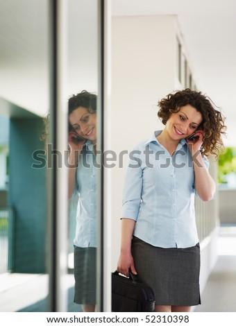 italian business woman talking on mobile phone outdoors and smiling. Vertical shape, copy space - stock photo