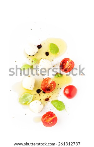 Italian caprese salad - modern artistic composition. Cherry tomatoes, mozzarella cheese, basil and olive oil on white background from above. Background layout with free text space. - stock photo