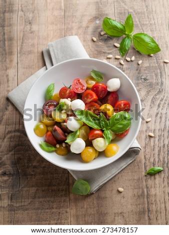 Italian Caprese salad with cherry tomatoes and mini mozzarella, selective focus - stock photo