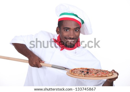 Italian chef with a pizza on a wooden peel - stock photo