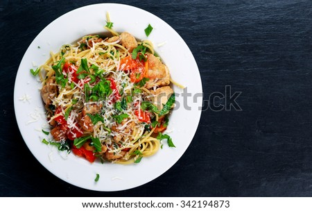 Italian Chicken Breast Pasta spaghetti with red pepper, Parmesan cheese and wild rocket  lives. on old blue stone table - stock photo