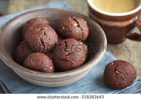 Italian chocolate cookies with walnuts and a cup of coffee on a wooden table, rustic style, selective focus - stock photo