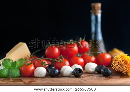 Italian classic ingredients for pasta with cheese, spaghetti and vegetables photographed from overside on black background with copy space. Shallow depth of field. - stock photo