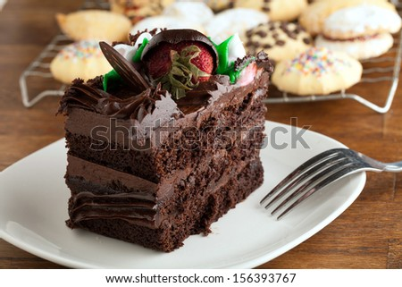 Italian cookies and a decadent slice of chocolate cake with iced flowers and chocolate covered strawberries on a plate with a fork. - stock photo