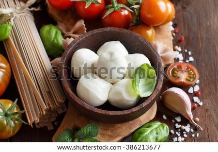Italian cooking ingredients : mozzarella, pasta, tomatoes, garlic, herbs and other - stock photo