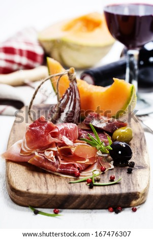 Italian cuisine. Antipasto. Prosciutto, melon, salami, olives and wine - stock photo