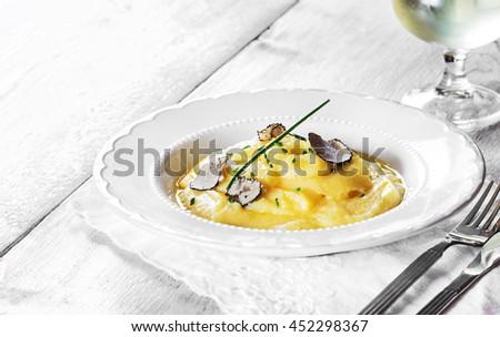 Italian cuisine- black truffle polenta on  white plate. Selective focus. - stock photo