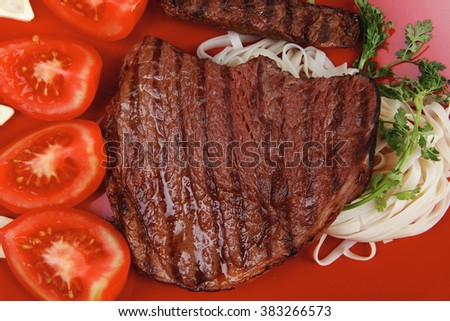 italian cuisine : grilled steak with pasta and tomatoes on red plate isolated over white background - stock photo