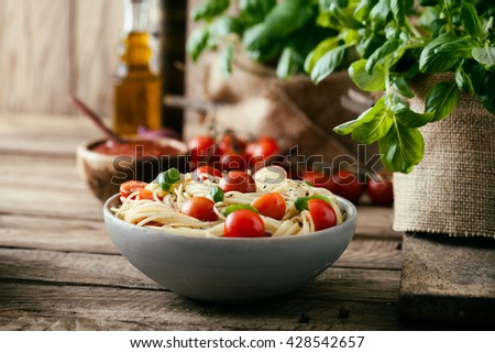 Italian cuisine. Pasta with olive oil, garlic, basil and tomatoes. Spaghetti with tomatoes - stock photo