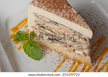 Italian dessert. Cake from ice cream mascarpone cheese chocolate. Decorated with mango sauce. - stock photo