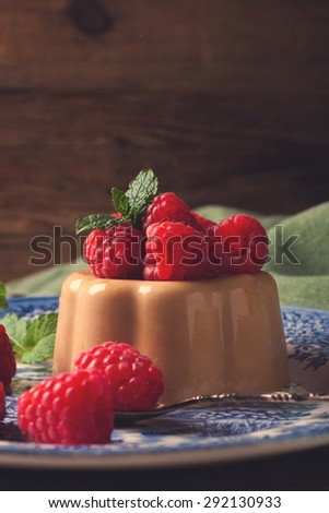 Italian dessert coffee panna cotta served on a blue plate with raspberries and fresh mint on vintage wooden background. Selective focus. Retro style toned.  - stock photo