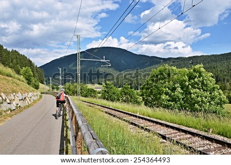 Italian Dolomites -cyclist on the cycle path along the railway - stock photo