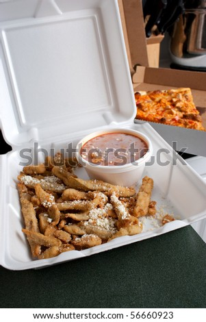 Italian fast food in takeout containers.  Pizza and fried battered eggplant strips. - stock photo