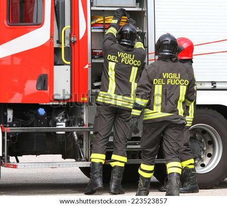 Italian firefighters working near the fire truck when handling an emergency - stock photo