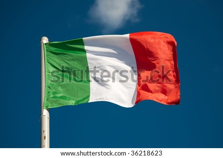 Italian flag against blue sky - stock photo