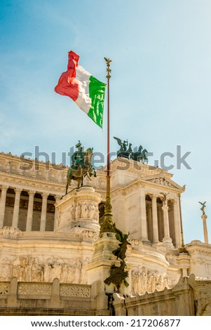 Italian flag on Vittoriano memorial in Rome. This monumental memorial for king Vittorio Emanuele II with guards was erected by Giuseppe Sacconi 1885 - 1911. - stock photo