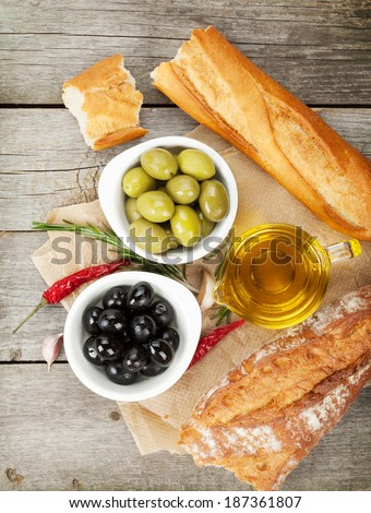 Italian food appetizer of olives, bread and spices on wooden table background - stock photo