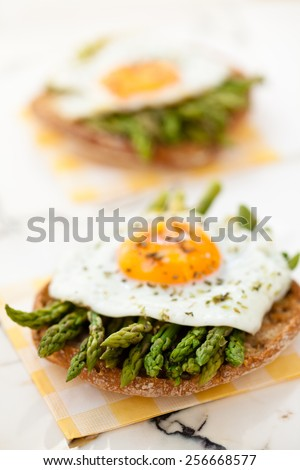 Italian food: appetizers with asparagus and fried eggs. Focus on  asparagus tips. - stock photo