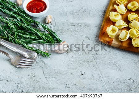 Italian food background with homemade raw tortellini, tomato sauce and rosemary over concrete textured board, place for text, border, selective focus. - stock photo