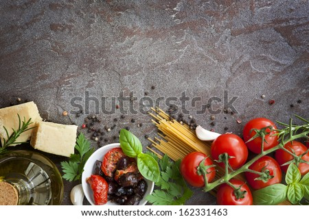 Italian food background, with vine tomatoes, basil, spaghetti, mushrooms, olives, parmesan, olive oil, garlic, peppercorns, rosemary, parsley and thyme.  Slate background. - stock photo