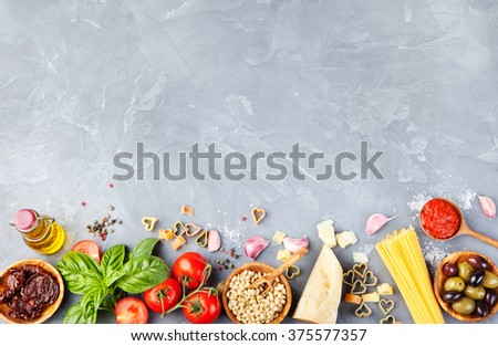 Italian food background with vine tomatoes, basil, spaghetti, olives, parmesan, olive oil, garlic Ingredients on stone table Copy space Top view - stock photo