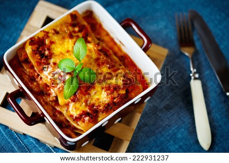 Italian Food. Hot tasty Lasagna plate served with fresh basil leaf. - stock photo