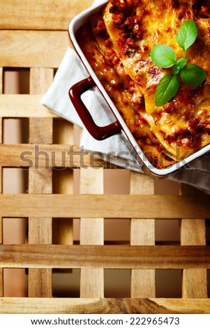 Italian Food. Hot tasty Lasagna plate served with fresh basil leaf. Wooden table background. Top view, space for your text. - stock photo