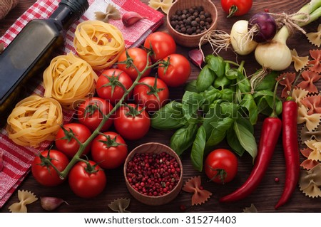 Italian food; ingredients for pasta; red tomatoes; vegetables and pasta on a wooden board; the substrate for the restaurant menu - stock photo