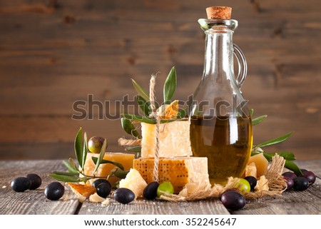 Italian food ingredients. Fresh olives, olive oil and parmesan cheese  on old wooden table.  - stock photo
