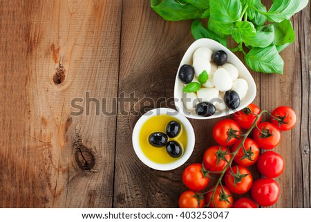 Italian food ingredients - tomatoes, basil, olives, olive oil, garlic, peppercorns and mozzarella on rustic wooden background, selective focus - stock photo