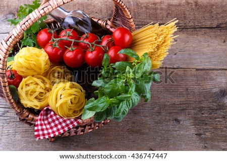Italian food pasta ingredients, basil, tomato,olive oil,parsley in a wicker basket on wooden background - stock photo