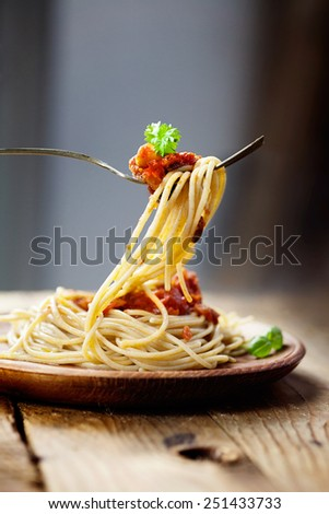 Italian food. Pasta spaghtti with tomato sauce, olives and garnish - stock photo